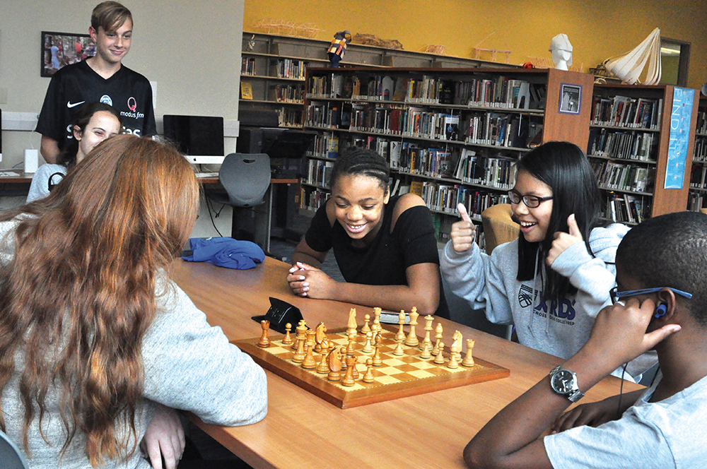 Crossroads students play chess during activity class