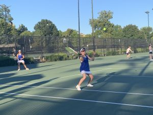 Crossroads girls' tennis team plays double match.